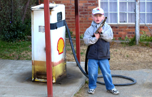 Carlton Smith aged 5, standing at Shell fuel pump on a farm in South Africa